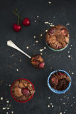 Chocolate cupcakes with cherries on dark backdrop. Stock Image