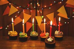 Chocolate cupcakes with candles against festive background Stock Image