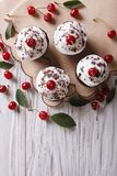 Chocolate cupcakes with cream and cherry vertical top view Stock Images