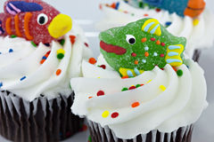 Chocolate cupcakes with fish decoration. Chocolate Cupcakes with vanilla frosting, sprinkles and a decorated candy fish on top on a blue plate royalty free stock images