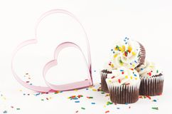 Chocolate Cupcakes with hearts. Four delicious stacked chocolate cupcakes with vanilla frosting and sprinkles on white background with two pink metal hearts copy Royalty Free Stock Photos