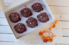 Chocolate cupcakes lay on white lace serviette near orange beads Royalty Free Stock Photography
