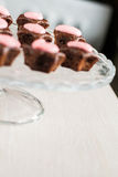 Chocolate cupcakes with pink stars-cream celebratory glass stand Royalty Free Stock Images