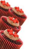 Chocolate cupcakes in red cups Royalty Free Stock Image