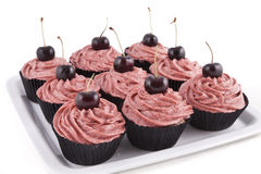 Chocolate cupcakes, with red frosting and a cherry. Chocolate flavored cupcakes, with red frosting and a cherry on top, on a white plate on white background Stock Image