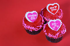 Chocolate cupcakes with red hearts, over red Royalty Free Stock Photo