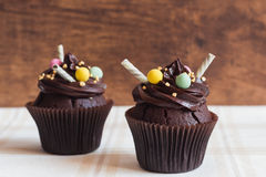 Chocolate cupcakes on rustic wooden background Stock Photography