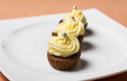 Chocolate cupcakes with silver sprinkles on top. Three chocolate cupcakes with silver sprinkles on top, on white plate and fabric tablecloth Stock Photos