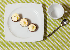 Chocolate cupcakes with silver sprinkles on top on white plate. Three chocolate cupcakes with silver sprinkles on top, on white plate and fabric tablecloth with Stock Photography