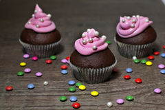 Chocolate cupcakes with strawberries cream. On wooden table Royalty Free Stock Photos