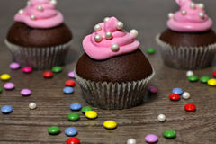 Chocolate cupcakes with strawberries cream. On wooden table Royalty Free Stock Images