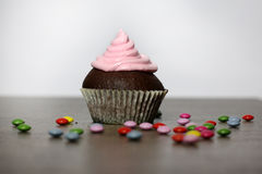 Chocolate cupcakes with strawberries cream. On wooden table Stock Images