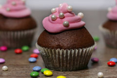 Chocolate cupcakes with strawberries cream. On wooden table Stock Photos