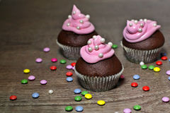 Chocolate cupcakes with strawberries cream. On wooden table Royalty Free Stock Image