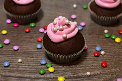 Chocolate cupcakes with strawberries cream. On wooden table Royalty Free Stock Photography