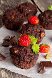 Chocolate cupcakes with strawberries on wooden background. Vertical Royalty Free Stock Photo