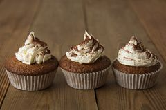 Chocolate cupcakes with whipped cream on rustic wooden table. Homemade dessert. royalty free stock photo