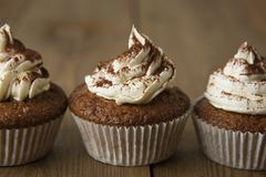 Chocolate cupcakes with whipped cream on rustic wooden table. Homemade dessert. stock image