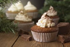 Chocolate cupcakes with whipped cream on rustic wooden table. Homemade dessert. stock photography