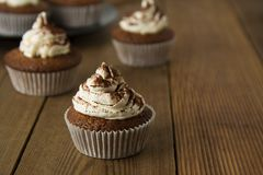 Chocolate cupcakes with whipped cream on rustic wooden table. Homemade dessert. Copy space. royalty free stock image