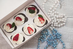 Chocolate cupcakes with white creme and strawberry on top in the. White box stock photos