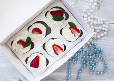 Chocolate cupcakes with white creme and strawberry on top in the. White box royalty free stock photos