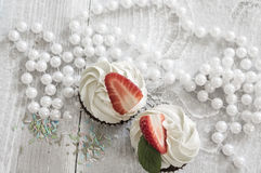 Chocolate cupcakes with white creme and strawberry on top in the. White box stock image
