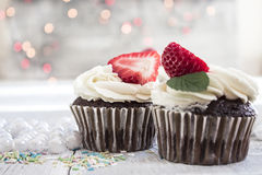 Chocolate cupcakes with white creme and strawberry on top in the. White box royalty free stock photography