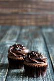 Chocolate cupcakes on wooden table Stock Photos