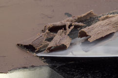 Chocolate curls are produced on a marble top Stock Images
