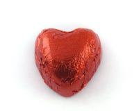 Chocolate dado forma coração na folha de estanho vermelha fotografia de stock royalty free