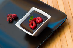 Chocolate dark pudding with raspberries Stock Image