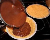Chocolate de derramamento na bandeja da torta enchida com a crosta do biscoito de Graham foto de stock royalty free