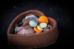 Chocolate de la forma del corazón con los dulces Foto de archivo libre de regalías