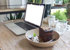 Chocolate de la torta en el trabajo de madera de la tabla con el ordenador portátil Imágenes de archivo libres de regalías