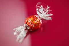 Chocolate de Lindt en fondo rojo Imágenes de archivo libres de regalías
