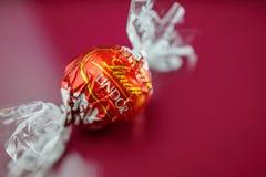 Chocolate de Lindt en fondo rojo Fotografía de archivo