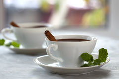 Chocolate del cacao en las tazas blancas con los palillos de cinamomo Foto de archivo libre de regalías