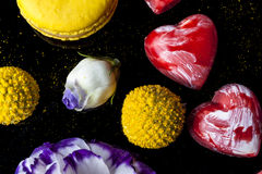Chocolate del corazón y flores y macarrones en negro desde arriba Fotos de archivo