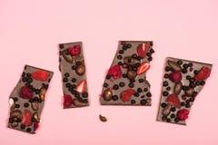 Chocolate delicioso com as porcas e os frutos isolados no rosa Fotos de Stock