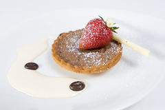 Chocolate dessert. Coffee and chocolate tart dessert with cream and strawberry garnish Stock Photo