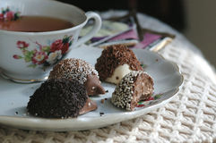 Chocolate for dessert. Chocolate candy with a cup of tea in an afternoon sun Stock Photo