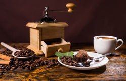 Chocolate dessert by coffee grinder and beans. Besides white mug on a wooden table Royalty Free Stock Photo