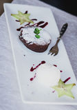 Chocolate dessert fondant with ice-cream and fruit. On a plate Stock Images