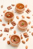 Chocolate dessert panna cotta in a small jars. Chocolate dessert panna cotta in glass jars with raw cocoa beans, top view stock images