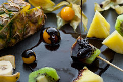 Chocolate Dipped Fruits. Fresh triopical fruits dipped in melted chocolate Stock Photography
