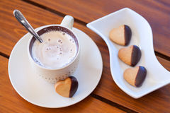 Chocolate dipped heart shaped shortbread cookies and a cup of ca Royalty Free Stock Images