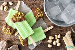 Chocolate dipped pistachio popsicles on rustic wood. Group of homemade chocolate dipped pistachio popsicles on a rustic wood background Stock Photo