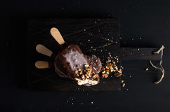 Chocolate dipped popsicles with chipped nuts on dark wooden board over black background Royalty Free Stock Images