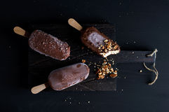 Chocolate dipped popsicles with chipped nuts on dark wooden board over black background Stock Photos